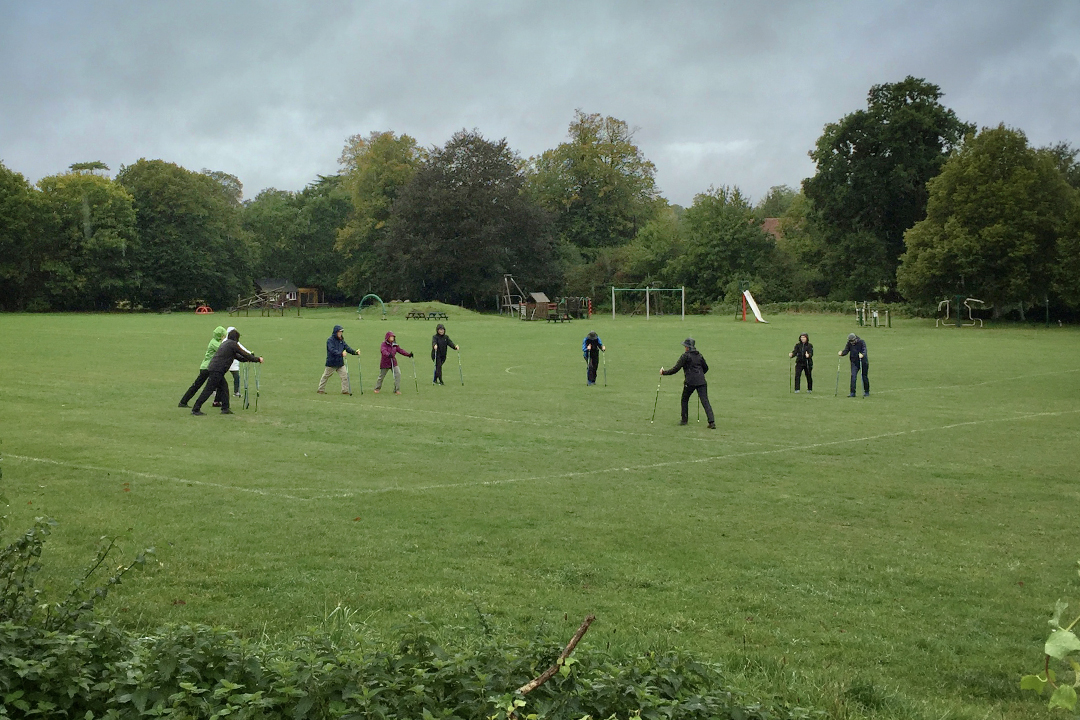 People socially distanced in a playing field learning Nordic Walking